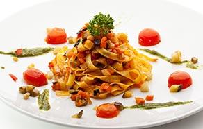 Tagliatelle vegetariane con pesto di rucola e pomodorini al forno